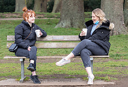 © Licensed to London News Pictures. 08/03/2021. London, UK. Students, Phoebe Aston 21 (left) and Nicole Wilson 20 from Wimbledon enjoy a coffee together for the first time since August 2020 on Wimbledon Common, South West London this morning. From today, (Monday 8th March 2021) two friends are now allowed to socialise out side of their household for a coffee or picnic for the first time in months. England begins Stage1 of the easing of lockdown today, with children returning to school, care homes allowing a visitor and friends being allowed to socialise out side of their bubble. However, pubs, shops and restaurants still remain closed. Photo credit: Alex Lentati/LNP