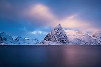 Winter sunrise on snow covered Olstind mountain peak rising from Fjord, Topp¯ya, Moskenes¯y, Lofoten Islands, Norway