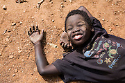 A young street child relaxing on the floor and enjoys the warmth of the winter sunshine in Harare, Zimbabwe.