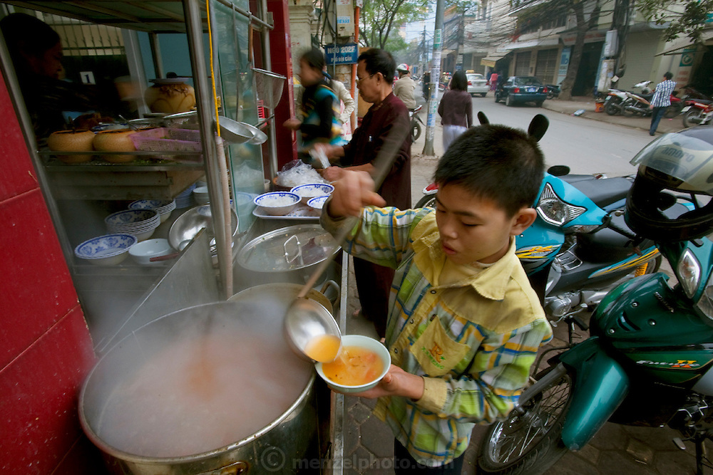 A young employee ladles breakfast pho into a bowl for a customer at a street pho noodle shop in Hanoi, Vietnam.