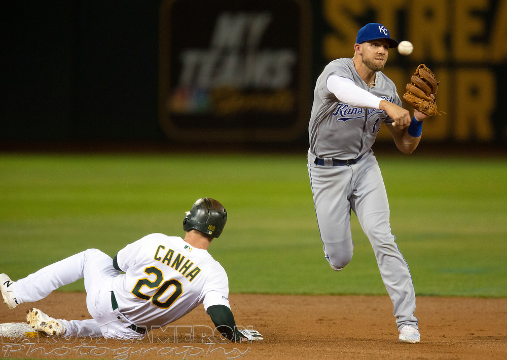 Sep 17, 2019; Oakland, CA, USA; Kansas City Royals third baseman Hunter Dozier (17) throws over Oakland Athletics Mark Canha (20) too late to double up Seth Brown at first during the second inning of a baseball game at Oakland Coliseum. Mandatory Credit: D. Ross Cameron-USA TODAY Sports