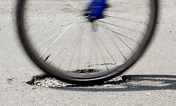 A cyclist rides over a pothole on a road in Kimberley, Nottingham