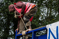 An anti-HS2 activist secured with a large rope around his neck blocks a HGV used for works connected to the HS2 high-speed rail link on 28 September 2020 in Denham, United Kingdom. Environmental activists continue to try to prevent or delay works on the controversial £106bn project for which the construction phase was announced on 4th September from a series of protection camps based along the route of the line between London and Birmingham.