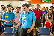16 FEBRUARY 2013 - BANGKOK, THAILAND:   ABHISIT VEJJAJIVA, former Prime Minister of Thailand, slides his ticket into the machine at the MoChit BTS station while  campaigning for his party colleague Sukhumbhand Paribatra ahead of Bangkok's governor election. Bangkok residents go to the polls on March 3 to elect a new governor. Sukhumbhand Paribatra, the current governor, is running on the Democrat's ticket and is getting help from national politicians like Abhisit Vejjajiva, the former Thai Prime Minister. One of Sukhumbhand's campaign pledges is to improve Bangkok's mass transit and transportation system. Abhisist road the BTS Skytrain to campaign for Sukhumbhand.    PHOTO BY JACK KURTZ