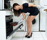 beautiful caucasian woman in a kitchen cooking an heart shape chocolate cake