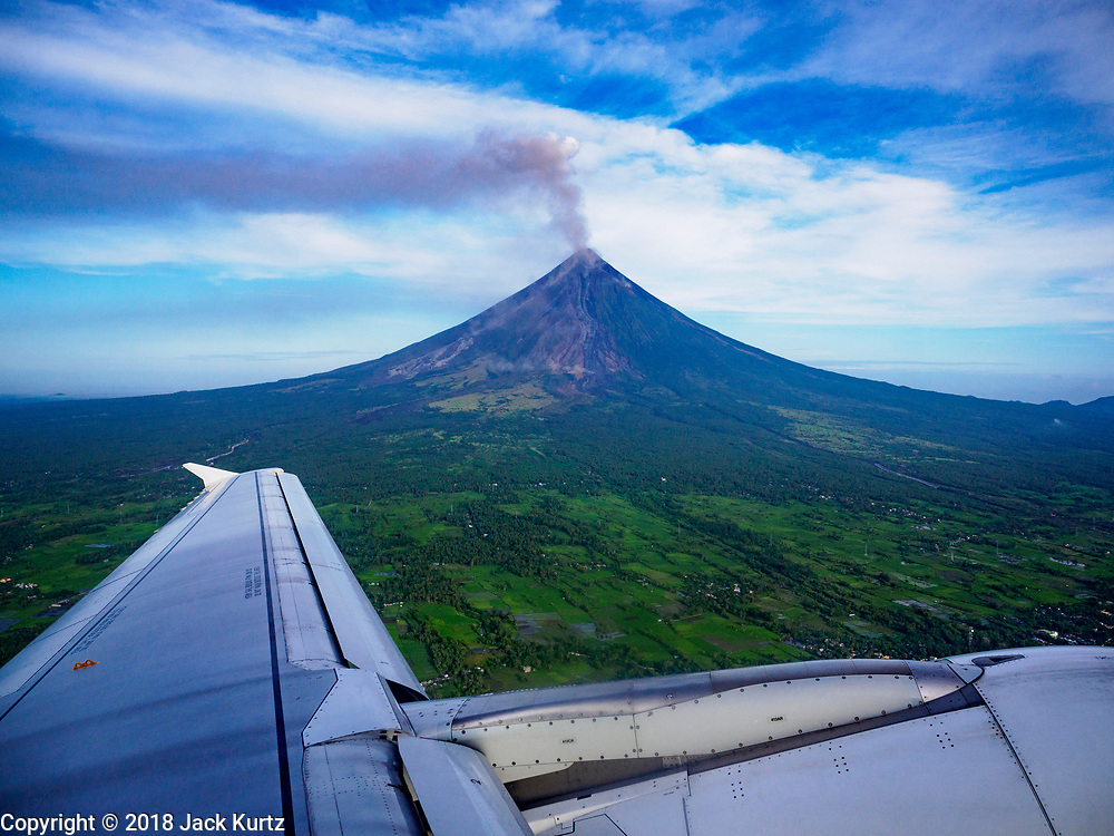 01 FEBRUARY 2018 - LEGAZPI, ALBAY, PHILIPPINES:  Philippine Express Airlines flight 2922, enroute Manila, an Airbus A320, flies past the Mayon volcano after departing Legazpi. The Mayon volcano started erupting in the middle of January. The airspace around the volcano has been closed off and on for more than week. The airport is about 13 kilometers from the volcano and the ash clouds from Mayon pose a threat to aircraft engines. More than 80,000 people have been evacuated from their homes around the volcano.    PHOTO BY JACK KURTZ