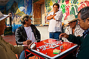 Men play dominoes among colorful murals in the town of Tepoztlan, Morelos state, Mexico on June 13, 2008.