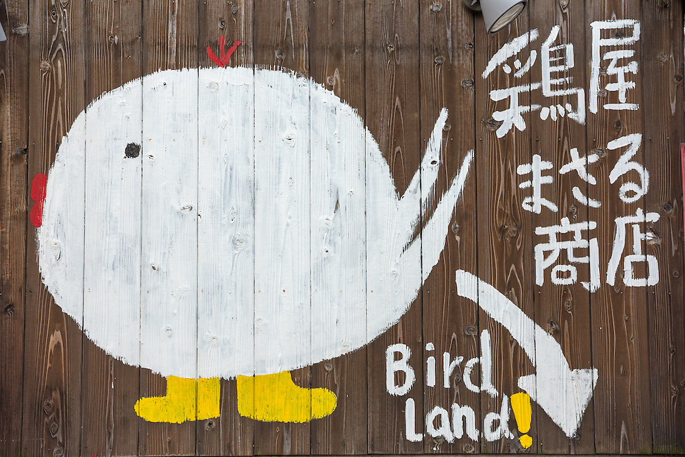Signage featuring a cartoon chicken advertising a local restaurant on Dotonbori in the Namba district of Osaka.