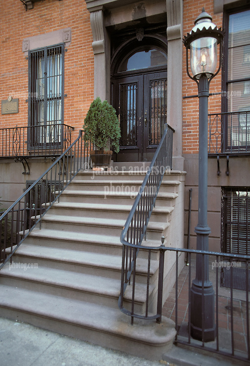 Stoop and Gas Light, Brick and Brown Stone Stairs to Wrought Iron Clad Doorway. No people. Brooklyn, New York City, February 25, 1976