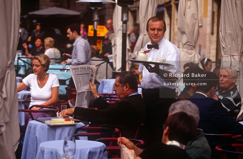 A waiter serves a pot of tea at his outdoor cafe in the Italian capital, on 3rd November 1999, in Rome, Italy.