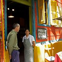 South America, Argentina, Buenos Aires. Parilla grill chef having conversation in doorway of La Boca restaurant.