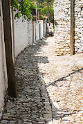 A narrow cobble stone street lined with white stone houses. Berat upper citadel old walled city. Albania, Balkan, Europe.