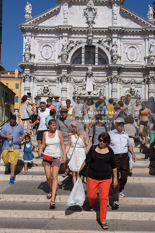 Tourist crowd descend steps over a bridge near a church in Venice, Italy.