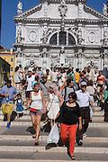 Tourist crowd descend steps over a bridge near a church in Venice, Italy.