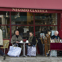 Two men with large shopping bags resting in the outdoor area of a cafe in Portobello Road Market, London