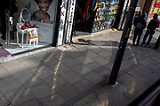 The reflections from a local beauty, hair and cosmetics business spills across the pavement on the Walworth Road in Southwark, on 27th February 2020, in London, England UK.