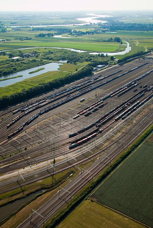 Nederland, Zuid-Holland, Zwijndrecht, 12-06-2009; Kijfhoek, rangeerterrein voor goederentreinen, overzicht van de verdeelsporen, met aan de horizon de Oude Maas. .De Betuweroute, die begint als Havenspoorlijn op de Maasvlakte, verbindt via Kijfhoek de Rotterdamse haven met het achterland. Kijkhoek huisvest Keyrail, exploitant Betuweroute en is in beheer bij ProRail.Het rangeeremplacement dient voor het sorteren van goederenwagons waarbij gebruik gemaakt wordt van de zwaartekracht, het heuvelen: de wagons worden de heuvel opgeduwd, bij het de heuvel afrollen komen ze, door middel van wissels, op verschillende verdeelsporen, railremmen zorgen voor het automatisch remmen van de wagons. Na het heuvelproces staan de nieuw samengestelde treinen op aparte opstelsporen..Kijfhoek, railway yard used by ProRail and Keyrail (Betuweroute operator). Kijfhoek connects via the Betuweroute (beginning as Havenspoorlijn on the Maasvlakte), through the port of Rotterdam with the hinterland. The shunting yard for sorting wagons makes use of gravity. The new trains are assembled on separate tracks.luchtfoto (toeslag), aerial photo (additional fee required).foto/photo Siebe Swart