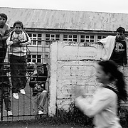 Children and young teenagers play in a housing estate in the heart of the small Romanian town of  Copsa Mica, Transylvania, Romania. Copsa Mica was once described as the most polluted town in Europe. May 8, 2008 Photo Tim Clayton...Copsa Mica, a small industrial town deep in Transylvania, Romania, was described during the 1990s as the most polluted town in Europe with lead levels reaching were more than 1000 times the allowable International limits and life expectancy nine years shorter than the National average...The pollution was caused entirely by two factories, Carbosin produced black for dies and tires and closed in 1993 while Sometra, a nonferrous smelter is still operational today...The pollution was so bad sheep were black, covered in soot and health officials advised against eating livestock or vegetables and drinking the water or milk...The Communist rule of Nicolae Ceausescu is blamed for the widespread environmental degradation that left industrial parts of Romania in ecological disaster. Industry was situated in a way to concentrate pollution in small areas leaving the rest of the country relatively free of pollution.Copsa Mica in particular was left an environmental disaster...The pollution caused a direct affect on human health with widespread Lung disease, Impotency, the highest infant mortality rate in Europe, Lead poisoning andbehavioral problems...Fifteen years on since the closure of Carbosin in 1993, the factory skeleton remains as part of the towns bleak landscape, Unfinished communist style housing blocks still stand in the heart of the towns housing estate. The town's inhabitants arestill trying to recover from the long lasting effects of pollution...Recent survey's found the soil contained so much lead that it was 92 times above the permitted level; the vegetation had a lead content 22 times above the permitted level. While toxins have penetrated at least one meter (three feet) into the soil leaving the entire food cha