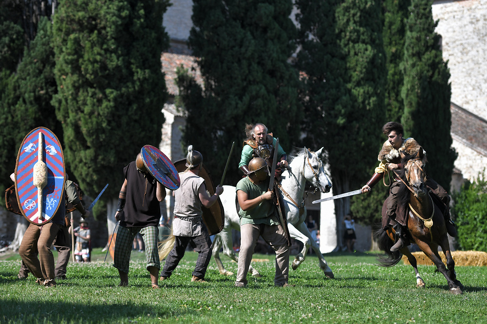 Aquileia, Italy - 17 June 2018: Celtic knights riding horses attack Roman villagers during Tempora in Aquileia, ancient Roman historical re-enactment