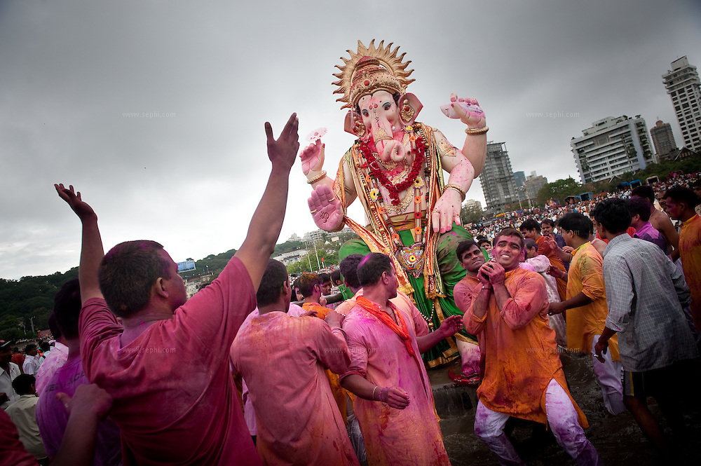 A group of Indian men, covered in red powder, carrying a huge idol of lord Ganesh into the sea for immersion in the Indian ocean on the last day of the Ganesh Chaturthi festival. Ganesh, the elephant-headed son of Shiva and Parvati is widely worshiped as the supreme God of wisdom, prosperity and good fortune. Mumbai, September 2009.