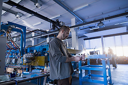 Young male engineer using mobile phone in an industrial plant, Freiburg im Breisgau, Baden-W¸rttemberg, Germany