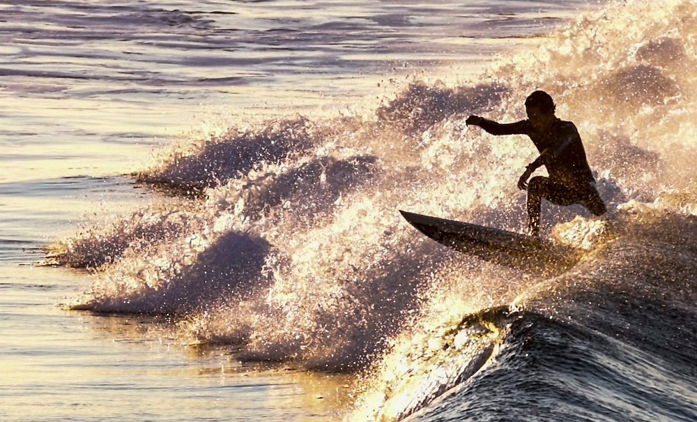 11/4/167:28:56 AM ---surfing----<br /> <br /> A surfer rides a wave as the sun rises at Huntington Beach on Nov. 4, 2016.<br /> <br /> Photo by Claire Rounkles, Sports Shooter Academy