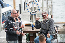 AJ and friends on his dock in the Methodist Circle in Weirs Beach during Laconia Motorcycle Week, New Hampshire, USA. Saturday June 17, 2017. Photography ©2017 Michael Lichter.