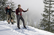 Two cross country skiers pause to look out into the fog along the Puyallup Ridge Trail of the Mount Tahoma Trails hut to hut cross country ski trail system near Mount Rainier in the Cascade Range of Washington, USA.