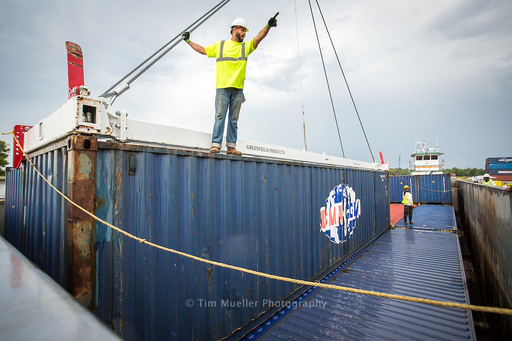 Port America longshoreman Kevin Murphy signals to the crane operator as he helps  guide a container onto a barge at the Port of Greater Baton Rouge Inland Rivers Marine Terminal. The containers are shipped by barge down the Mississippi River to the Port of New Orleans.