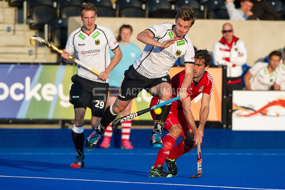 Great Britain's Adam Dixon is tackled by Mats Grambusch of Germany. Great Britain v Germany, Lee Valley Hockey & Tennis Centre, London, UK on 14 April 2015. Photo: Simon Parker