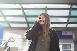 Young woman talking on mobile phone and smiling, Freiburg im Breisgau, Baden-Württemberg, Germany