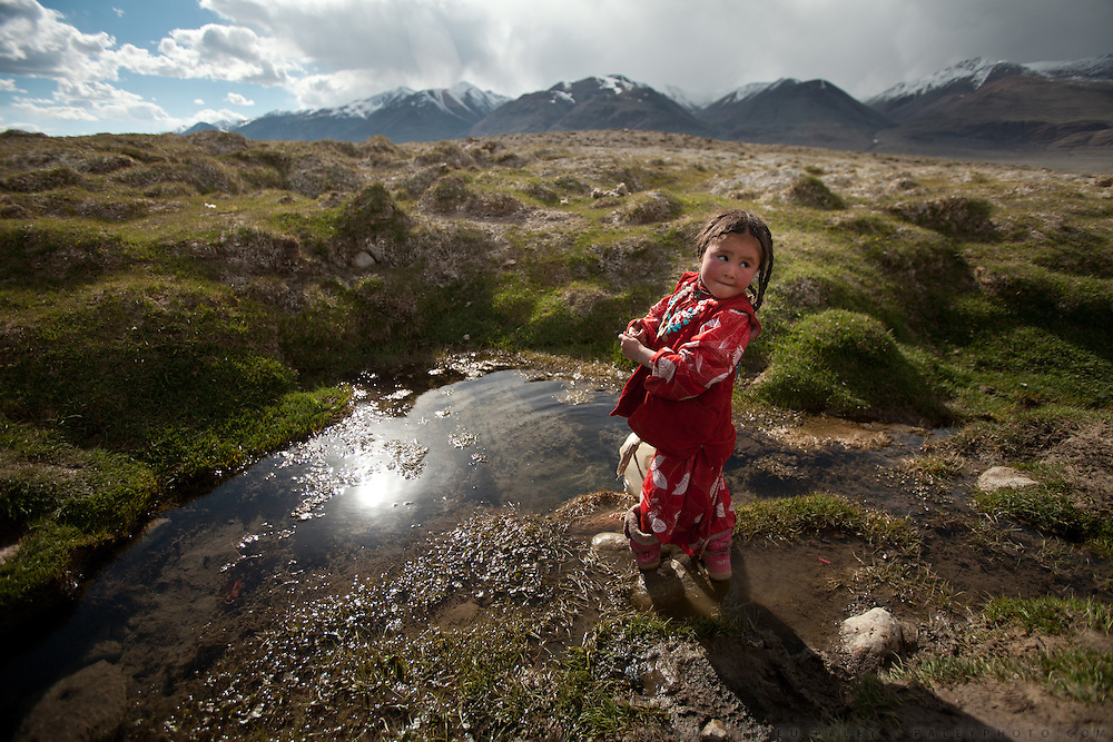 Six-year old Susaï is fetching water near camp in a spring claimed as one of the sources of the Oxus, also known as Amu Darya, Central Asia's largest river.  Its waters define most of Afghanistan's borders with other nations to the north..Summer camp of Muqur, Er Ali Boi's place...Trekking through the high altitude plateau of the Little Pamir mountains (average 4200 meters) , where the Afghan Kyrgyz community live all year, on the borders of China, Tajikistan and Pakistan.