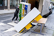 A contractor struggles with unstable office locker furniture being removed from from a nearby building during the third lockdown of the Coronavirus pandemic, in the City of London, the capitals financial district, on 10th February 2021, in London, England.