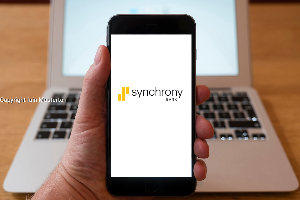 Using iPhone smartphone to display logo of Synchrony Bank, , an American online bank