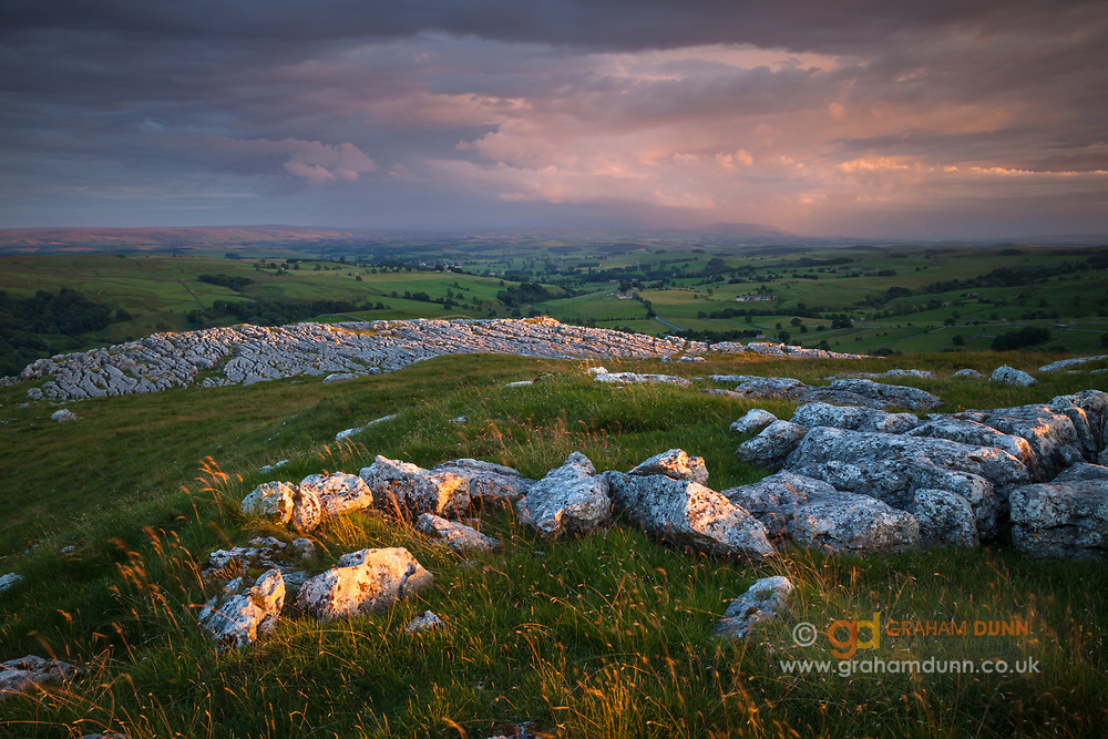 Golden evening light catches the limestone pavement on Broad Flats, Malham, whilst dramatic stormy skies hover over Pendle Hill in the distance. A dramatic sunset scene in the Yorkshire Dales, England, UK.