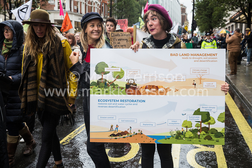 London, UK. 12 October, 2019. A climate activist from Extinction Rebellion holding a board explaining the concepts of bad land management and ecosystem restoration takes part in the XR funeral march from Marble Arch to Russell Square on the sixth day of International Rebellion protests to demand a government declaration of a climate and ecological emergency, a commitment to halting biodiversity loss and net zero carbon emissions by 2025 and for the government to create and be led by the decisions of a Citizens' Assembly on climate and ecological justice. Credit: Mark Kerrison/Alamy Live News