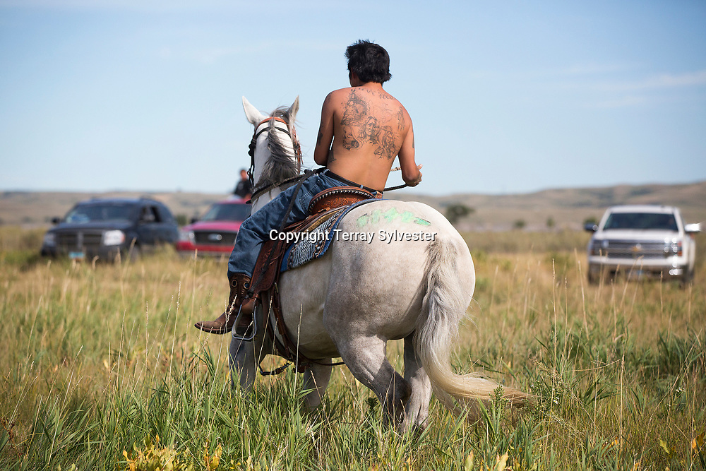 A man rides a horse through the opposition camp against the Dakota Access oil pipeline on September 11, 2016. Cannon Ball, North Dakota, United States.