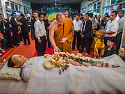 12 OCTOBER 2104 - BANG BUA THONG, NONTHABURI, THAILAND:  A Buddhist monk pours scented water over the hand of Apiwan Wiriyachai on the first day of his funeral rites at Wat Bang Phai in Bang Bua Thong, a Bangkok suburb, Sunday. Apiwan was a prominent Red Shirt leader, member of the Pheu Thai Party of former Prime Minister Yingluck Shinawatra, and a member of the Thai parliament. The military government that deposed the elected government in May, 2014, charged Apiwan with Lese Majeste for allegedly insulting the Thai Monarchy. Rather than face the charges, Apiwan fled Thailand to the Philippines. He died of a lung infection in the Philippines on Oct. 6. The military government gave his family permission to bring him back to Thailand for the funeral. He will be cremated later in October. The first day of the funeral rites Sunday drew tens of thousands of Red Shirts and their supporters, in the first Red Shirt gathering since the coup.   PHOTO BY JACK KURTZ