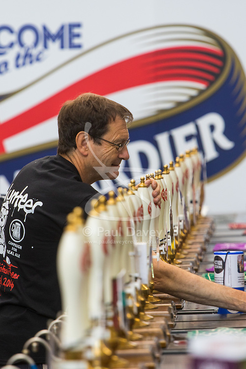Olympia, London, August 9th 2015. Hundreds of real ale lovers attend the Campaign for Real Ale  Great British Beer Festival at London's Olympia Exhibition Centre, where dozens of independent breweries demonstrate the diversity of British brewed beers. PICTURED: Dozens of beer pumps dispense beer to the crowds.