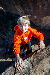 Boy climbing boulders at Hueco Tanks State Park & Historic Site, El Paso, Texas. USA.