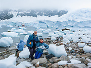 "Tom and Carol Dempsey visit the continent of Antarctica at Neko Harbor, Graham Land, Antarctic Peninsula. We cruised here on the red and white ship M/S Explorer in February 2005 and made a wet landing using Zodiac boats. Glaciers calve icebergs into the Southern Ocean. An adult Gentoo Penguin (Pygoscelis papua) has a bright orange-red bill and a wide white stripe extending across the top of its head. Chicks have grey backs with white fronts. Of all penguins, Gentoos have the most prominent tail, which sweeps from side to side as they waddle on land, hence the scientific name Pygoscelis, ""rump-tailed."" As the the third largest species of penguin, adult Gentoos reach 51 to 90 cm (20-36 in) high. They are the fastest underwater swimming penguin, reaching speeds of 36 km per hour. Published in November/December 2008 Sierra Magazine, Sierra Club Outings. For licensing options, please inquire."