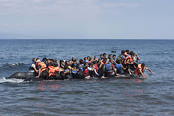Aug. 25, 2015 - Lesbos, Greece - An inflatable boat carrying some fifty refugees approaches the shore on the northeastern part of Lesvos. More than 30,000 refugees have reached the Greek island of Lesvos during August 2015, according to Amnesty International. (Credit Image: © Nikolas Georgiou/ZUMA Wire)