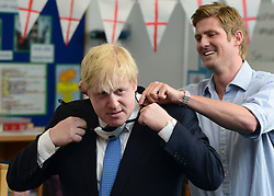 """© Licensed to London News Pictures. 23/04/2013. London, UK Teacher, Ed Wickstead helps Boris Johnson fit the """"sound field"""" microphone for the lesson. Mayor of London, Boris Johnson takes part in a Year 6 Class about St George's Day at Tidehall Academy in Deptford, South East London today 23rd April 2013. The class was taught by """"Outstanding Teacher"""" Ed Wickstead. During the lesson Mr jOhnson wore a """"sound field"""" device around his neck so his voice could be heard by the class. Photo credit : Stephen Simpson/LNP"""