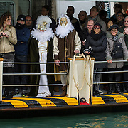 VENICE, ITALY - FEBRUARY 16:  Two masks  stand on a Waterbus during the passage of the traditional regatta which officially opens the Venice Carnival  on February 16, 2014 in Venice, Italy. The 2014 Carnival of Venice will run from February 15 to March 4 and includes a program of gala dinners, parades, dances, masked balls and music events.  (Photo by Marco Secchi/Getty Images)