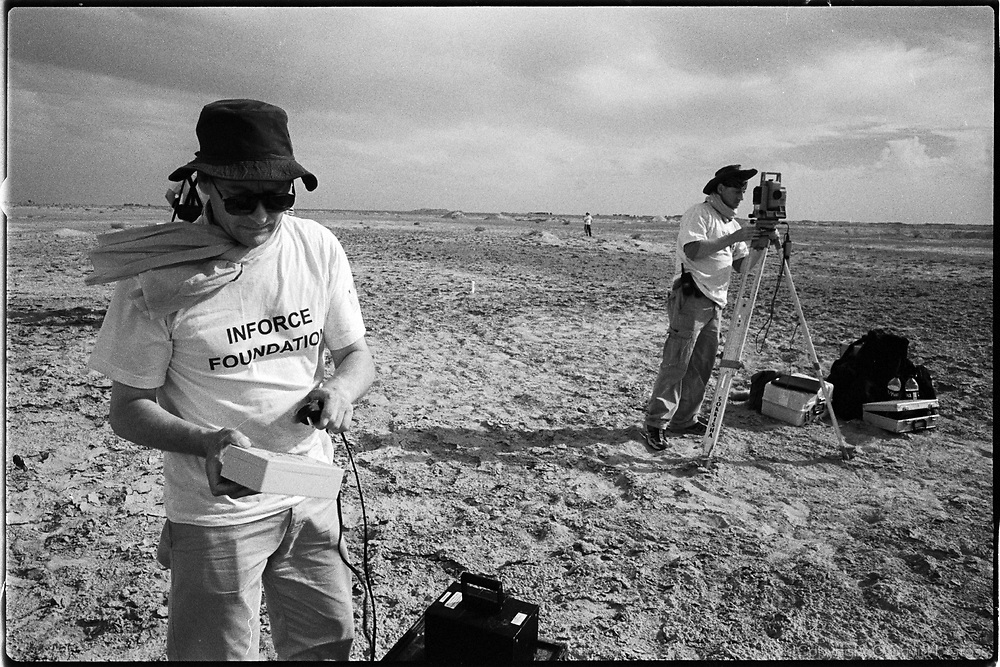 """Members of Inforce, a UK team of """"grave hunters"""", set up the GPS/laser surveying system, preparing to scan the soil for disturbance to check for the presence of a mass grave, near Al-Musayab, Iraq. This was the first time the ensemble of high-tech geological tools had been employed to look for a mass grave."""
