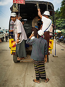 """25 OCTOBER 2015 - INSEIN, MYANMAR:  An old truck converted to a bus picks up passengers at Danyin Market (also known as Da Nyin) in Insein, Myanmar, about 90 minutes from Yangon. Vendors in the market sell just about everything people in the area need, but mostly it's a """"wet market"""" with fruits, vegetables and meats. Most people in Myanmar still do not have refrigerators in their homes, so people go to market almost every day.    PHOTO BY JACK KURTZ"""