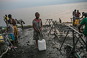 A girl readies to carry a water container in which she fetched the water from the city-run water stand next to the Kivu Lake.