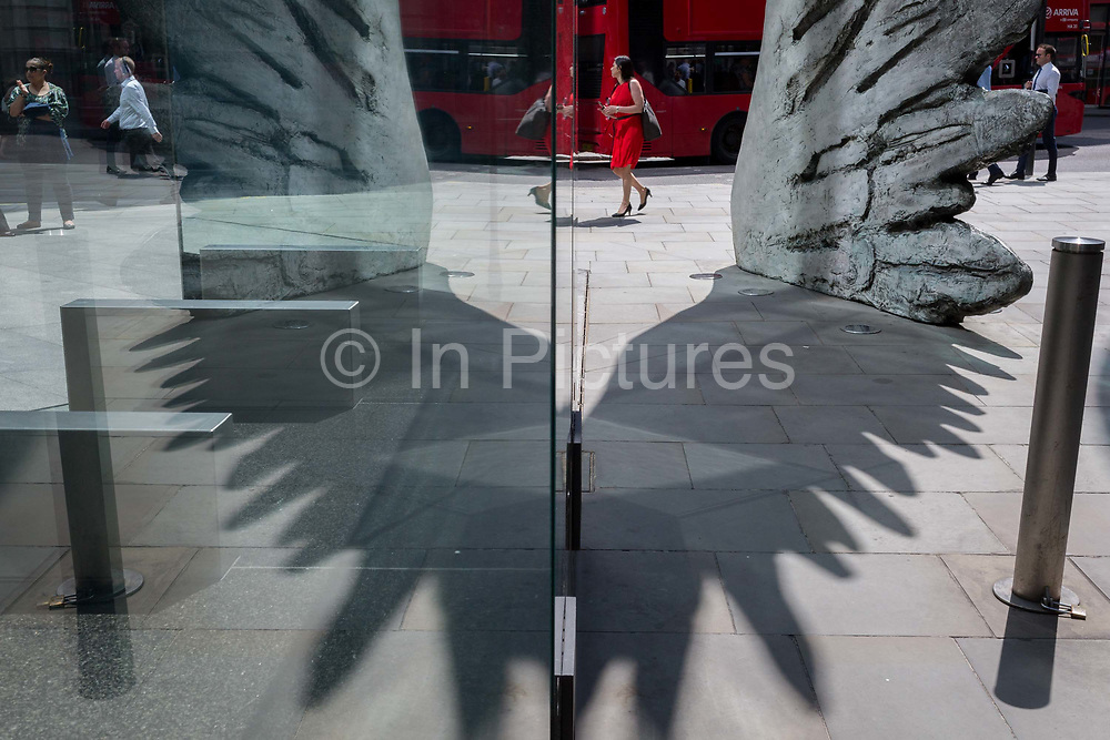 A financial industry businesswoman in red walks past the sculpture entitled City Wing on Threadneedle Street in the City of London, the capitals financial district aka the Square Mile, on 11th July 2019, in London, England. City Wing is by the artist Christopher Le Brun. The ten-metre-tall bronze sculpture is by President of the Royal Academy of Arts, Christopher Le Brun, commissioned by Hammerson in 2009. It is called 'The City Wing' and has been cast by Morris Singer Art Founders, reputedly the oldest fine art foundry in the world.