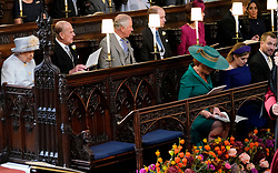 Queen Elizabeth II, the Duke of Edinburgh, Prince of Wales, the Duke and Duchess of Cambridge, the Duke and Duchess of Sussex, sit behind Sarah, Duchess of York, Princess Beatrice and Peter Phillips, at the wedding of Princess Eugenie to Jack Brooksbank at St George's Chapel in Windsor Castle.