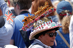 A member of the public wears a themed hat outside Buckingham Palace, central London, following the Trooping the Colour ceremony as the Queen celebrates her official birthday today.